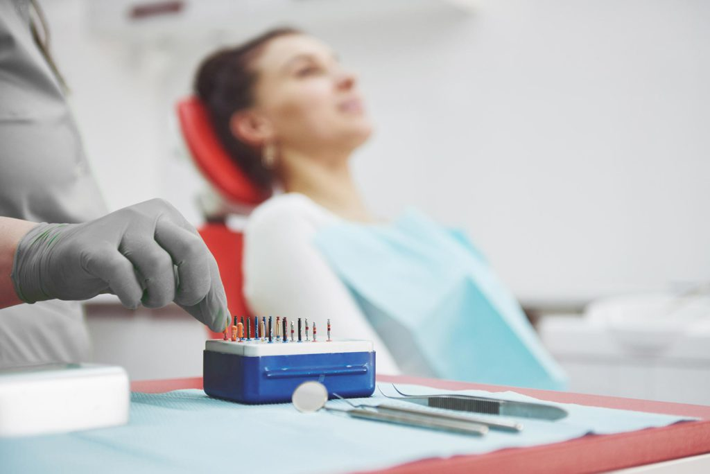 a-patient-in-a-dental-clinic-sits-in-a-chair-and-t-JV4YJVX
